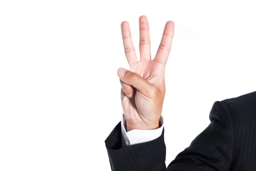 指三本を立てている手