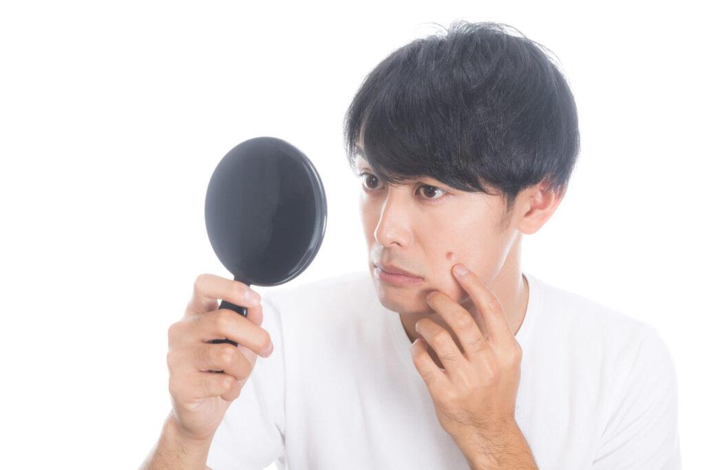 手鏡でニキビを確認する男性