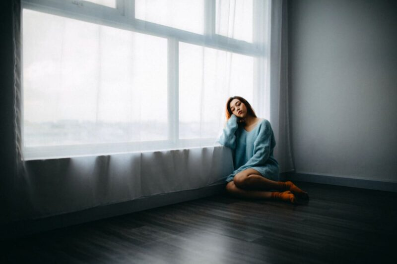 窓辺で座り込む女性